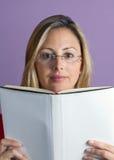 Γυναίκα που διαβάζει σε ένα βιβλίο την άσπρη κάλυψη Στοκ εικόνες με δικαίωμα ελεύθερης χρήσης