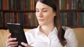 Γυναίκα που διαβάζει στο σπίτι EBook Έγγραφο εναντίον της ψηφιακής ανάγνωσης, ε-βιβλία που αντικαθιστά τα φυσικά βιβλία τυπωμένων απόθεμα βίντεο
