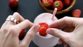Γυναίκα που διακοσμεί milkshake με τις φρέσκες φράουλες φιλμ μικρού μήκους