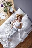 Γυναίκα που διαρρέει στο κρεβάτι Στοκ Εικόνα