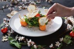 Γυναίκα που δοκιμάζει το πιάτο εστιατορίων στο άσπρο πιάτο στο γκρίζο υπόβαθρο Στοκ Εικόνα