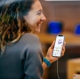 Γυναίκα που δοκιμάζει Animoji στο πιό πρόσφατο iPhone Χ στη Apple Store Στοκ Εικόνα