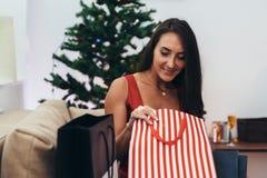 Γυναίκα που εγκαθιστά από το χριστουγεννιάτικο δέντρο και που παίρνει ένα παρόν από την τσάντα αγορών στοκ φωτογραφία με δικαίωμα ελεύθερης χρήσης
