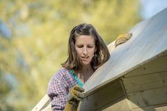 Γυναίκα που εγκαθιστά μια στέγη σε μια ξύλινη καλύβα κήπων Στοκ φωτογραφία με δικαίωμα ελεύθερης χρήσης