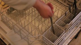 Γυναίκα που εκκενώνει το πλυντήριο πιάτων Γυναίκα που κάνει τις μικροδουλειές σπιτιών Πιάτα μαζέματος με το χέρι γυναίκας από το  απόθεμα βίντεο