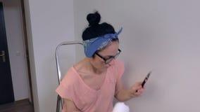 Γυναίκα που ελέγχει τον τοίχο μετά από να χρωματίσει απόθεμα βίντεο