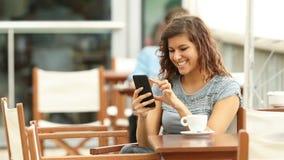 Γυναίκα που ελέγχει το έξυπνο τηλέφωνο σε έναν φραγμό απόθεμα βίντεο