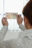 Γυναίκα που ελέγχει το υδατόσημο τραπεζογραμματίων Στοκ εικόνα με δικαίωμα ελεύθερης χρήσης