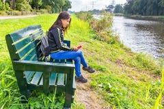 Γυναίκα που ενεργοποιεί το κινητό τηλέφωνο στον πάγκο στον ποταμό στοκ εικόνες