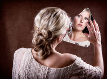 Γυναίκα που εξετάζει έναν σπασμένο καθρέφτη Στοκ φωτογραφία με δικαίωμα ελεύθερης χρήσης