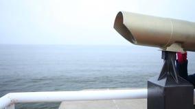 Γυναίκα που εξετάζει μέσω των διοπτρών τουριστών τη θάλασσα απόθεμα βίντεο