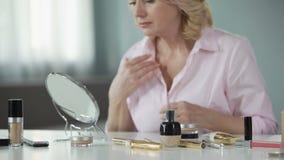 Γυναίκα που εξετάζει προσεκτικά το γηράσκον και κρεμώντας δέρμα της που συλλογίζεται για την ανύψωση απόθεμα βίντεο
