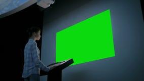 Γυναίκα που εξετάζει την κενή μεγάλη διαλογική επίδειξη τοίχων - πράσινη έννοια οθόνης απόθεμα βίντεο