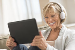Γυναίκα που εξετάζει την ψηφιακή ταμπλέτα χρησιμοποιώντας τα ακουστικά Στοκ εικόνες με δικαίωμα ελεύθερης χρήσης