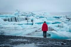 Γυναίκα που εξετάζει τη λιμνοθάλασσα παγετώνων Jokulsarlon στην Ισλανδία Στοκ Εικόνες