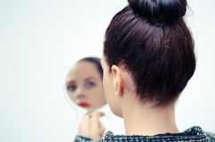 Γυναίκα που εξετάζει τη μόνη αντανάκλαση στον καθρέφτη Στοκ φωτογραφία με δικαίωμα ελεύθερης χρήσης