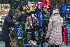 Γυναίκα που εξετάζει τις μπλούζες με το Vladimir Putin σε μια μικρή αγορά Στοκ φωτογραφία με δικαίωμα ελεύθερης χρήσης