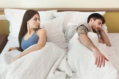Γυναίκα που εξετάζει τον άνδρα ενώ αυτός ύπνος μετά από τη φιλονικία Στοκ Εικόνα