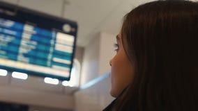 Γυναίκα που εξετάζει τον πίνακα επίδειξης αερολιμένων, που ελέγχει την κινηματογράφηση σε πρώτο πλάνο κατάστασης πτήσης αναχώρηση απόθεμα βίντεο