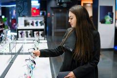 Γυναίκα που εξετάζει το έξυπνο ρολόι στο σύγχρονο κατάστημα στοκ φωτογραφία