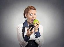 Γυναίκα που εξετάζει το έξυπνο τηλέφωνο που τρώει το μήλο στοκ φωτογραφίες