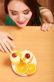 Γυναίκα που εξετάζει το εύγευστο γλυκό κέικ gluttony Στοκ Εικόνα