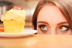 Γυναίκα που εξετάζει το εύγευστο γλυκό κέικ gluttony Στοκ φωτογραφία με δικαίωμα ελεύθερης χρήσης