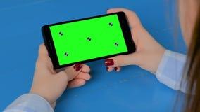 Γυναίκα που εξετάζει το μαύρο smartphone με την κενή πράσινη οθόνη - βασική έννοια χρώματος απόθεμα βίντεο