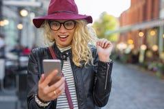 Γυναίκα που εξετάζει το smartphone της στην ευχάριστη έκπληξη Στοκ Εικόνα