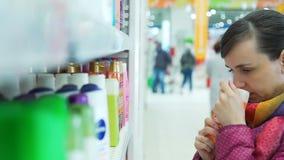 Γυναίκα που επιλέγει ένα σαμπουάν σε μια υπεραγορά απόθεμα βίντεο