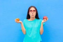 Γυναίκα που επιλέγει μεταξύ ανθυγειινό Muffin και της υγιούς Apple στοκ φωτογραφία με δικαίωμα ελεύθερης χρήσης