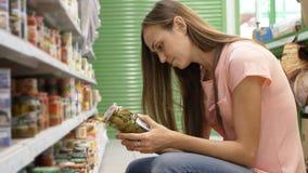 Γυναίκα που επιλέγει τα κονσερβοποιημένα τρόφιμα από τα ράφια στην υπεραγορά και που διαβάζει την ετικέτα στοκ φωτογραφίες