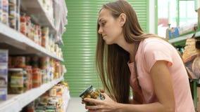 Γυναίκα που επιλέγει τα κονσερβοποιημένα τρόφιμα από τα ράφια στην υπεραγορά και που διαβάζει την ετικέτα Στοκ φωτογραφία με δικαίωμα ελεύθερης χρήσης
