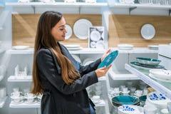 Γυναίκα που επιλέγει τα πιάτα εργαλείων σε μια υπεραγορά καταστημάτων στοκ φωτογραφία με δικαίωμα ελεύθερης χρήσης