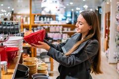 Γυναίκα που επιλέγει τα πιάτα εργαλείων σε μια υπεραγορά καταστημάτων στοκ φωτογραφία