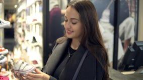 Γυναίκα που επιλέγει τα υποδήματα παπουτσιών των παιδιών σε ένα κατάστημα υπεραγορών καταστημάτων απόθεμα βίντεο