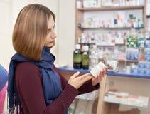 Γυναίκα που επιλέγει τα φάρμακα στο φαρμακείο στοκ εικόνα με δικαίωμα ελεύθερης χρήσης