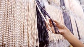 Γυναίκα που επιλέγει τις χειροποίητες χάντρες μαργαριταριών στο κατάστημα κοσμήματος 4K φιλμ μικρού μήκους