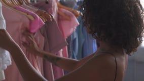 Γυναίκα που επιλέγει το φόρεμα στη μπουτίκ απόθεμα βίντεο
