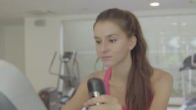 Γυναίκα που επιλύει στο ποδήλατο άσκησης στη γυμναστική Θηλυκό που ασκεί στο ποδήλατο απόθεμα βίντεο