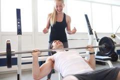 Γυναίκα που επισημαίνει τον άνδρα που ανυψώνει Barbell στη γυμναστική Στοκ Εικόνες