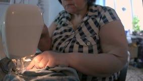 Γυναίκα που επισκευάζει τα τζιν που χρησιμοποιούν μια ράβοντας μηχανή, πυροβολισμός κινηματογραφήσεων σε πρώτο πλάνο φιλμ μικρού μήκους