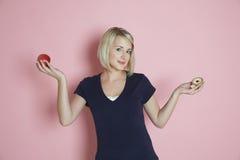 Γυναίκα που επιλέγει μεταξύ της Apple και ξινή Στοκ φωτογραφία με δικαίωμα ελεύθερης χρήσης