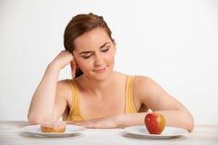 Γυναίκα που επιλέγει μεταξύ της Apple και Doughnut για το πρόχειρο φαγητό Στοκ Εικόνες
