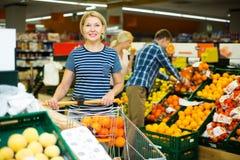 Γυναίκα που επιλέγει τα εποχιακά φρούτα Στοκ εικόνα με δικαίωμα ελεύθερης χρήσης