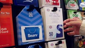 Γυναίκα που επιλέγει την κάρτα δώρων του Esso πενήντα δολαρίων φιλμ μικρού μήκους