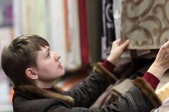 Γυναίκα που επιλέγει τις κουρτίνες στοκ φωτογραφίες με δικαίωμα ελεύθερης χρήσης