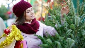 Γυναίκα που επιλέγει το δέντρο του νέου έτους στην έκθεση απόθεμα βίντεο