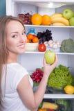 Γυναίκα που επιλέγει το μήλο στο σύνολο ψυγείων νόστιμου Στοκ εικόνα με δικαίωμα ελεύθερης χρήσης