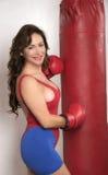 Γυναίκα που επιλύει με τα γάντια και ένα punchbag Στοκ Εικόνες